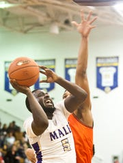 Male guard Tyren Moore storms toward the basket and past the outstretched arms of Fern Creek guard Darrius Washington. 