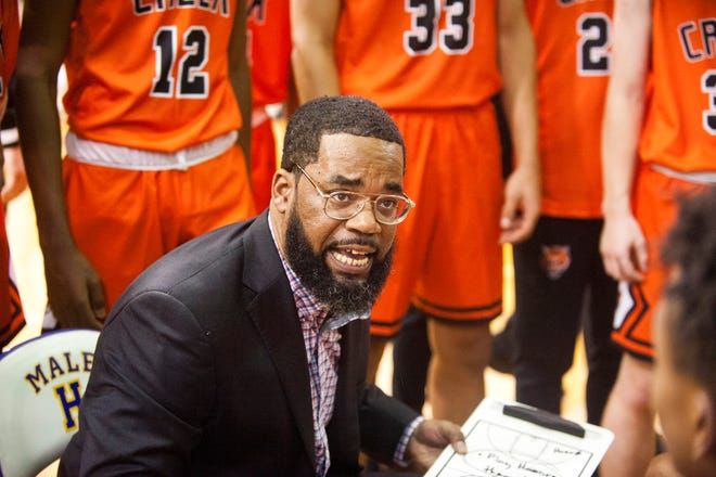 Fern Creek head basketball coach James Schooler, III talks to his players during a time-out.10 December 2019