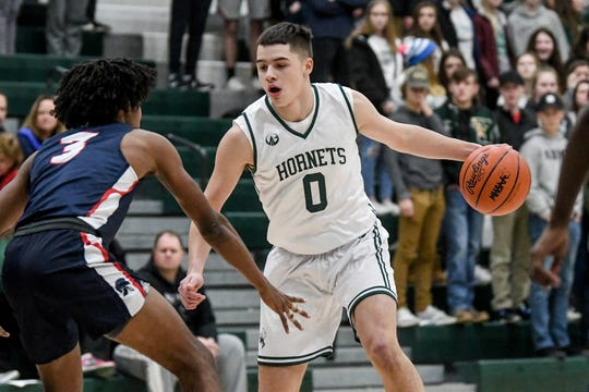 Williamston's Jacob Wallace, right, looks for room as East Lansing's Andrel Anthony defends during the first quarter on Tuesday, Dec. 10, 2019, at Williamston High School.