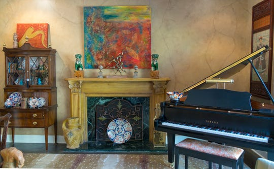The piano in the living room was a gift from Gary Beard's parents. The custom painting above the fireplace is by local artist and gallery owner, Tom Clifton, and serves as art, as well as a screen for a hidden television.
