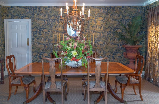 The dining room is a mix of styles including Chinoiserie wallpaper, an antique English double pedestal Regency mahogany dining table with a wide satinwood veneer band, an oval hand-carved English pine mirror, c. 1920, and a chandelier from Graham's Lighting.