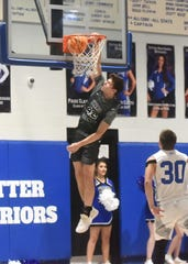 Izard County's Justus Cooper goes up for a slam against Cotter on Tuesday night.