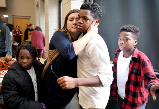 Franktown Open Hearts Director of Program Operations Crystal Tinnon hugs student Teavon Hartwell as he and other students eat a Thanksgiving meal together at Christ Community Church in Franklin on Wednesday, Nov. 26, 2019.