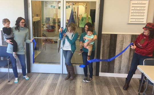 """Amber Pierson officially cuts the ribbon, opening """"Better Together Playnasium"""" at at 5089 York Road, while her mother, Mary Poole, and her son, Kai, inspiration for the enterprise, look on Dec. 11."""