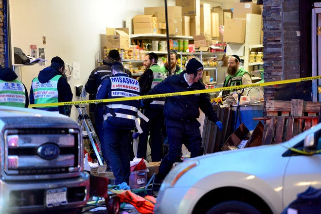 A clean up crew sifts through the debris at the Jersey City Kosher Supermarket the morning after a shoot out with police in Jersey City, N.J. on Wednesday Dec. 11, 2019. One police officer, the two shooters and three civilians were killed.