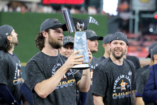 Gerrit Cole #45 of the Houston Astros celebrates with the trophy following his teams 6-4 win against the New York Yankees in game six of the American League Championship Series at Minute Maid Park on October 19, 2019 in Houston, Texas.