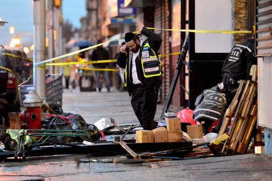 A cleanup crew sifts through the debris at the Jersey City Kosher Supermarket on Dec. 11, the morning after a shootout between armed attackers and police.