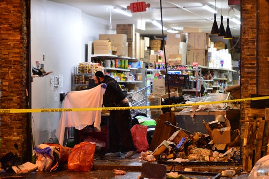 A clean up crew sifts through the debris at the Jersey City Kosher Supermarket after a shoot out with police in Jersey City, N.J. on Wednesday Dec. 11, 2019. One police officer, the two shooters and three civilians were killed.