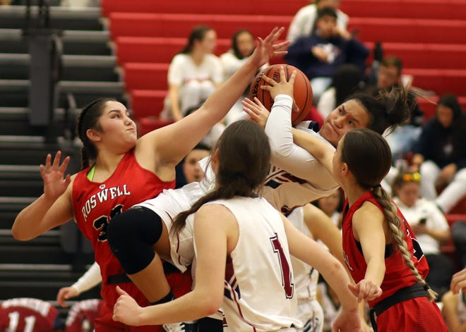 Sophomore Lady 'Cat Harmanie Dominguez is almost parallel to the floor on this hard drive to the basket Tuesday against Roswell High. Dominguez scored a season-high 25 points to lead Deming High to a 61-51  victory.