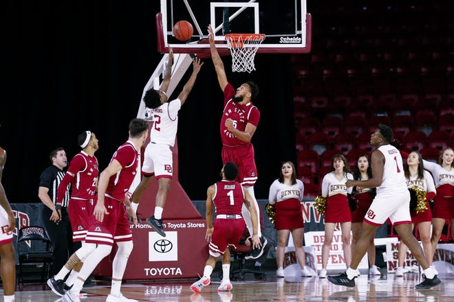 New Mexico State Aggies forward Johnny McCants (35) blocks the shot of Denver Pioneers guard Roscoe Eastmond (2) in the first half at Magness Arena in Denver, Colorado.