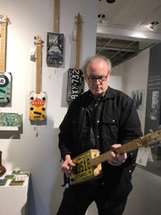 The guitars with three strings made by John Reichel, which features license plates or cigar boxes, were popular at the Holiday Shop. Reichel plays a tune on one of them.
