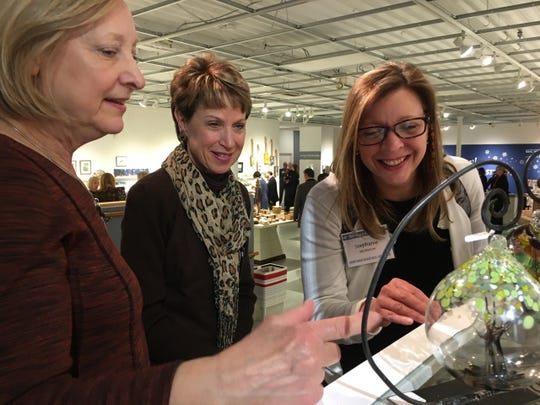 (From left) Gale McGuire, Dale Frankel and Stephanie McMahon examine a beautiful blown glass ornament at the Birmingham Bloomfield Art Center made by John Boyett.