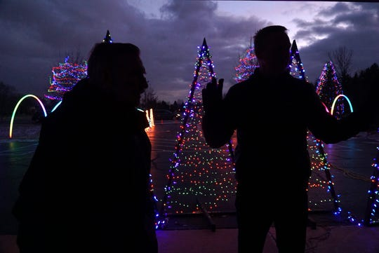 Ken Howse, left, with Livonia Lights, and Lead Pastor Brooks McElhenny of Northville Christian Assembly are silhouetted against the lights as they talk about the Northville Township's thrice-weekly Symphony of Lights Show at the Six Mile Road house of worship. The shows are performed Friday, Saturday and Sundays starting at 6 pm through Dec. 22nd. Howse used to run the light show in his Livonia neighborhood but managing the crowds are much easier at the large church grounds.