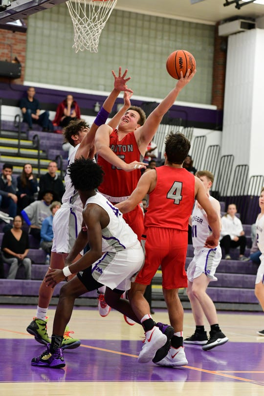 Canton's Jake Vickers drives in for a basket against Pioneer while teammate Ben Stesiak watches.