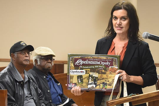 Opelousas Tourism Director Melanie LeBouef displays an Opelousas-Opoly game Tuesday night during a meeting of the Board of Aldermen. Businesses selling the board game which is played in a way similar to Monopoly, say the item has been a quick sale at their stores.