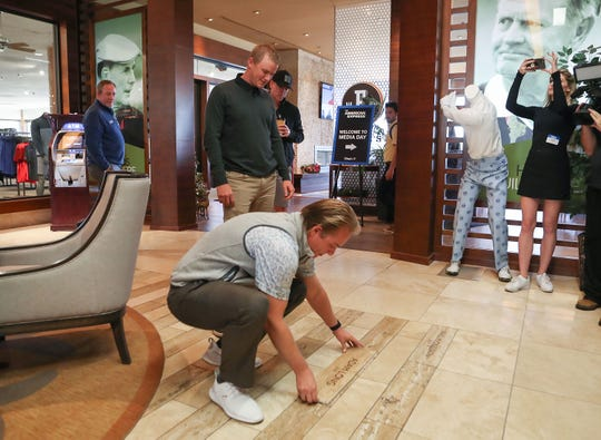 Defending champion Adam Long, standing, is helped by PGA West pro Sam Varner in  picking out the spot for his name to be installed among those of other past champions of the American Express golf tournament in the clubhouse at PGA West in La Quinta, December 11, 2019.