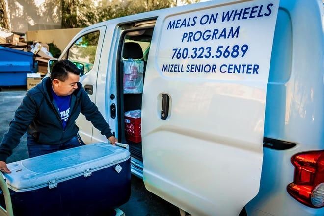 Staff member Juan Colorado loads meals into the Meals on Wheels van.