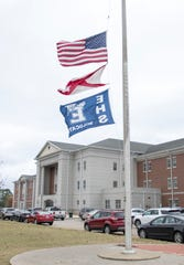 Flags fly at half-staff Tuesday outside Enterprise High School in Alabama in honor of Joshua Kaleb Watson, one of the victims of the deadly attack at NAS Pensacola.