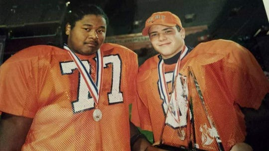 Current Escambia wide receivers coach Erik Lee (77) and Brett Gilliland stand with their state runner-up medals at the University of Florida after the 1999 Class 4A state championship game when Escambia faced St. Thomas Aquinas. It was the last state championship appearance for Escambia.