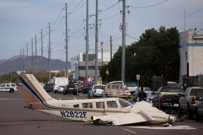 Police officers and FAA officials work the scene of a Piper PA-34 plane crash near 23rd Avenue and Deer Valley Road in Phoenix on Dec. 11, 2019. The pilot was the only person on the plane and was not injured.