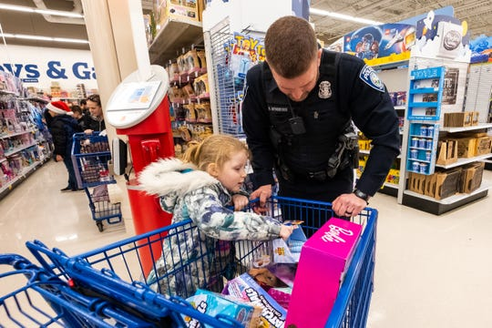 Port Huron Police Officer Ryan Minsberge helps Jaklyn Gross, 5, sort through a shopping cart full of toys during the annual Christmas With A Cop event Tuesday, Dec. 10, 2019, at the Fort Gratiot Meijer.