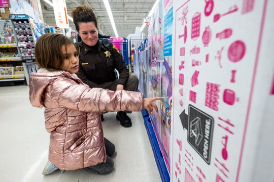 St. Clair County Sheriff Road Patrol Officer Keri Duva listens while Ariyah Holt, 6, tries to decide which Barbie house to buy during the annual Christmas With A Cop event Tuesday, Dec. 10, 2019, at the Fort Gratiot Meijer.