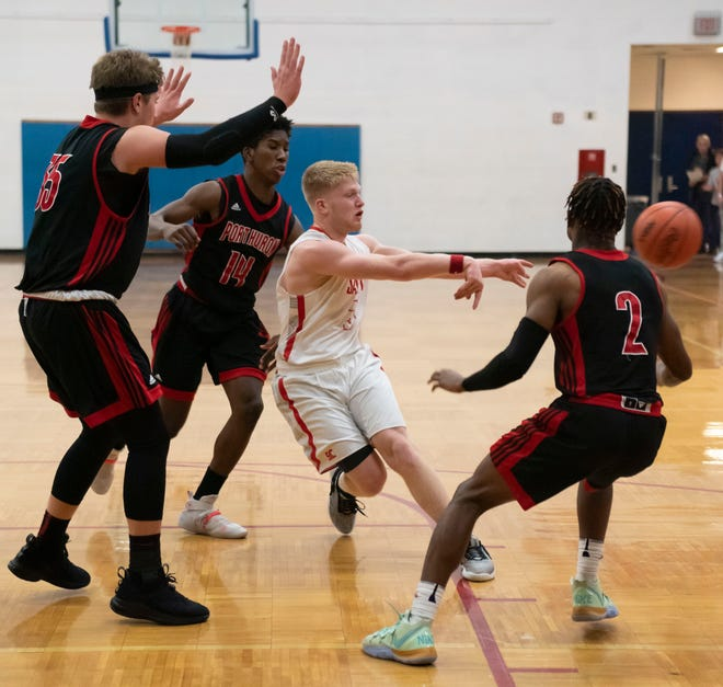 St Clair's Sean Donaldson passes the ball as three defenders, Jace Mullins, Shaka Brown-Thomas and NiJere Finney crowd him Tuesday, Dec. 10 during their basketball game against Port Huron High at St. Clair High School.