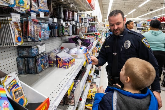 Clay Township Police Officer Dave Fajardo helps Franklin Gross, 7, choose a pack of Pokemon cards during the annual Christmas With A Cop event Tuesday, Dec. 10, 2019, at the Fort Gratiot Meijer.