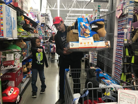 "Jeremy Renner shops with Sebastian Villaflores, 10, at Walmart in South Reno for ""Shop with the Sheriff"" on Dec. 10, 2019."