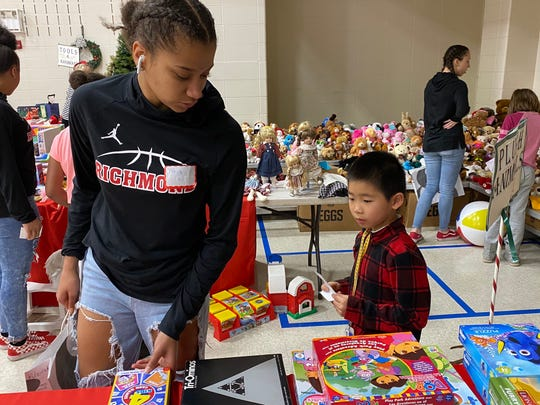 Richmond junior Alayha Allen helps a boy at the Boys and Girls Club of Wayne County's Christmas Shop pick out a gift.