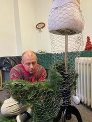 Jonathan Hampton works on a mermaid-themed Christmas tree for the 'Tis the Season display in St. Paul's Episcopal Church.