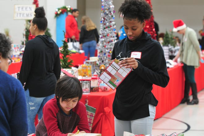 Richmond sophomore Jayci Allen helps a boy at the Boys and Girls Club of Wayne County's Christmas Shop pick out a gift.