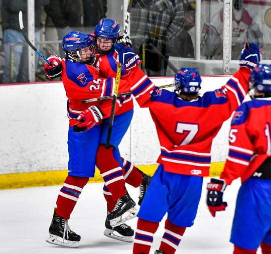 Fairport's Nick Krug, left, congratulates Sam Hoyen on scoring the Red Raiders' second goal against McQuaid during a regular season game at the Rochester Ice Center, Tuesday, Dec. 10, 2019.