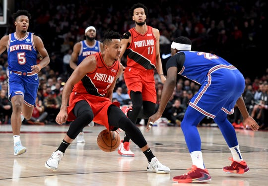 Portland Trail Blazers guard CJ McCollum, front left, dribbles the ball on New York Knicks guard Damyean Dotson, right, as guard Dennis Smith Jr., back left, closes in during the second half of an NBA basketball game in Portland, Ore., Tuesday, Dec. 10, 2019. The Blazers won 115-87.