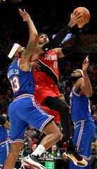 Portland Trail Blazers forward Carmelo Anthony, center, drives to the basket on New York Knicks forward Marcus Morris Sr., left, and center Mitchell Robinson, right, during the second half of an NBA basketball game in Portland, Ore., Tuesday, Dec. 10, 2019. The Blazers won 115-87.