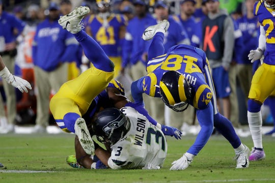 Seattle Seahawks quarterback Russell Wilson (3) is sacked by Los Angeles Rams linebacker Obo Okoronkwo, left, and linebacker Travin Howard during the second half of an NFL football game Sunday, Dec. 8, 2019, in Los Angeles.