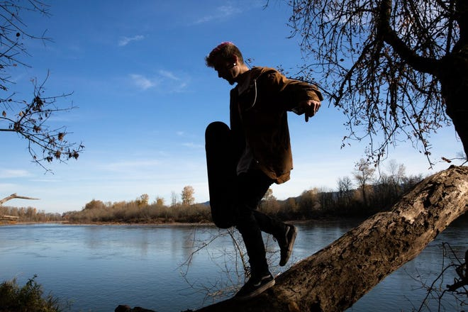 Caleb climbs a tree near his adult foster home on Monday, Nov. 11, 2019, in Oregon. He says this spot on the Willamette River is meditative and important to him because he can't see any man-made buildings or structures from there.