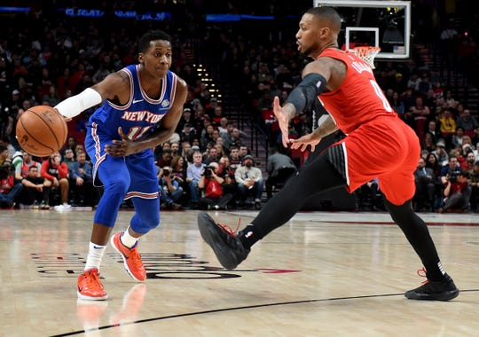New York Knicks guard Frank Ntilikina, left, passes the ball around Portland Trail Blazers guard Damian Lillard during the first half of an NBA basketball game in Portland, Ore., Tuesday, Dec. 10, 2019.