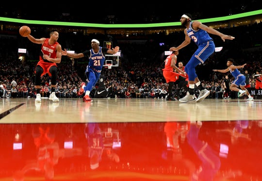 Portland Trail Blazers guard CJ McCollum, left, dribbles the ball on New York Knicks guard Damyean Dotson, center, as center Mitchell Robinson, right, closes in during the second half of an NBA basketball game in Portland, Ore., Tuesday, Dec. 10, 2019. The Blazers won 115-87.