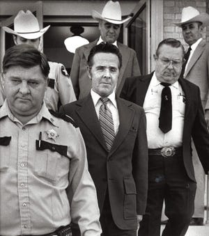 Henry Lee Lucas is surrounded by law enforcement escorting him from the Tom Green County Jail on the second day of a murder trial in this archived photo from April 3, 1984.