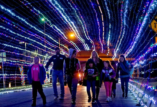 A group of visitors to the Tour of Lights in San Angelo make their way through the tunnel Monday, Dec. 10, 2019.