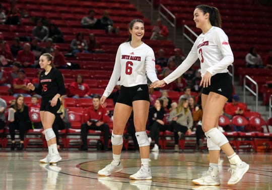 Elizabeth Juhnke taps hands with Sami Slaughter between volleys in the quarterfinals of the National Invitational Volleyball Championship on Tuesday, Dec. 10, at the Sanford Coyote Sports Center in Vermillion.