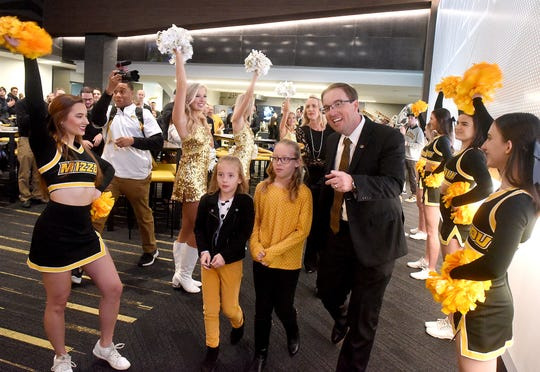 University of Missouri's new head football coach Eliah Drinkwitz escorts his daughters Emerson, 6, Addison, 9, and wife Lindsey, center, into the Show-Me Club in the south end zone facility at Memorial Stadium Tuesday where he was introduced to the media and the public.