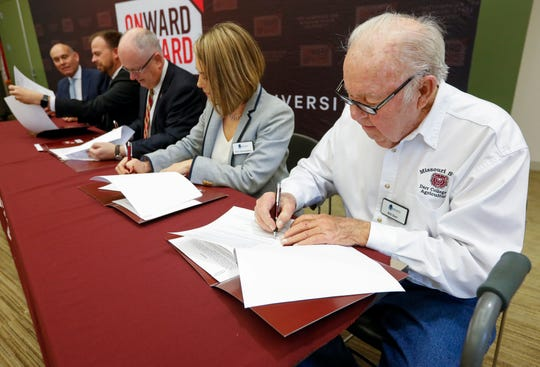 Bill Darr, right, founder of the Darr Family Foundation, signs a document giving $6.5 million from the foundation to build a new six-classroom agricultural magnet school near the MSU College of Agriculture.