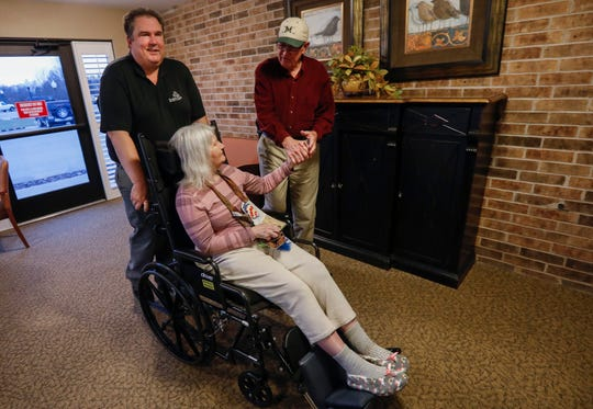 John Alexander, right, and Mark Applegate take Brenda Alexander back to her room at the nursing home she lives at in Greene County.