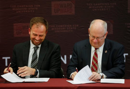 Springfield Public Schools Superintendent John Jungmann, left, and Missouri State University President Clif Smart sign a document giving $6.5 million from the Darr Family Foundation to build a new six-classroom agricultural magnet school near the MSU College of Agriculture.