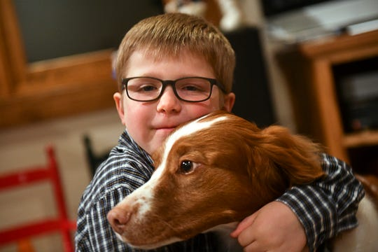 Ethan Haus hugs family dog Remington Tuesday, Dec. 10, 2019,  at his home near Clear Lake.