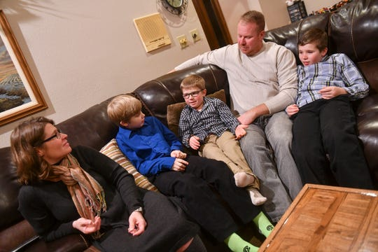 Ethan Haus, center, talks about his experiences with his parents Sheri and Dan and brothers Brady and Cole during an interview Tuesday, Dec. 10, at their home.