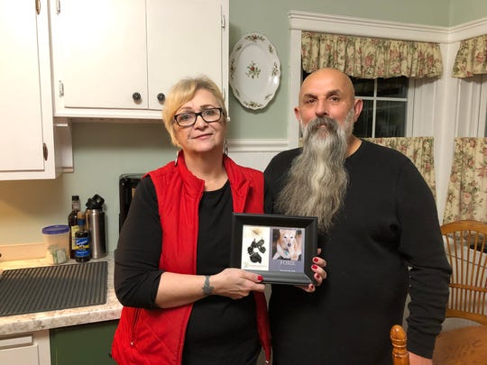 Jean and Joe Bjerke stand in their kitchen with a photo of their dog, Foxie. Foxie would keep Jean Bjerke company in the kitchen when she baked.