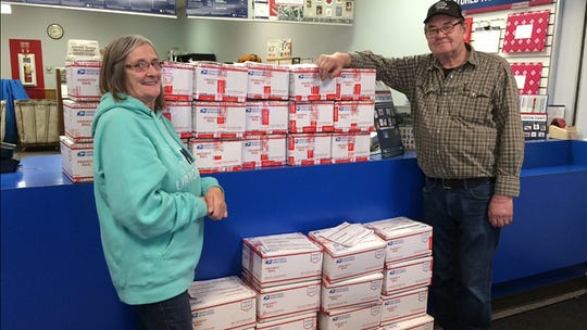 Becky Carlson and Slim Carlson mail hundreds of care packages to troops serving overseas Wednesday, Dec. 11, at the Waite Park post office.